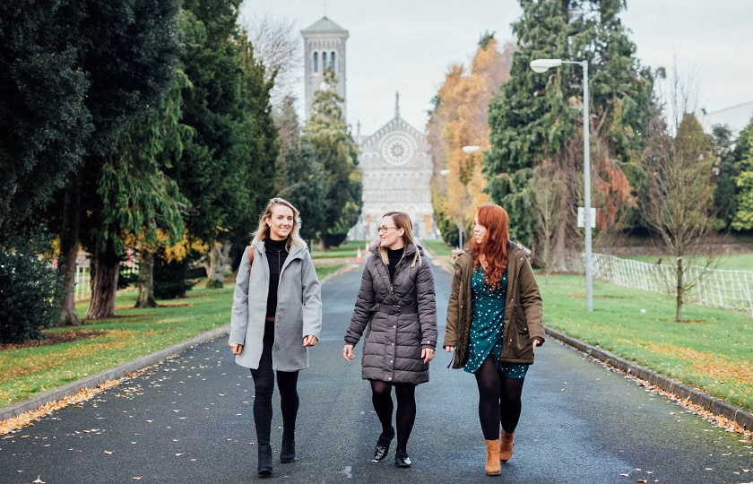 3 female students walking towards MIC Thurles with Thurles Cathedral in the background