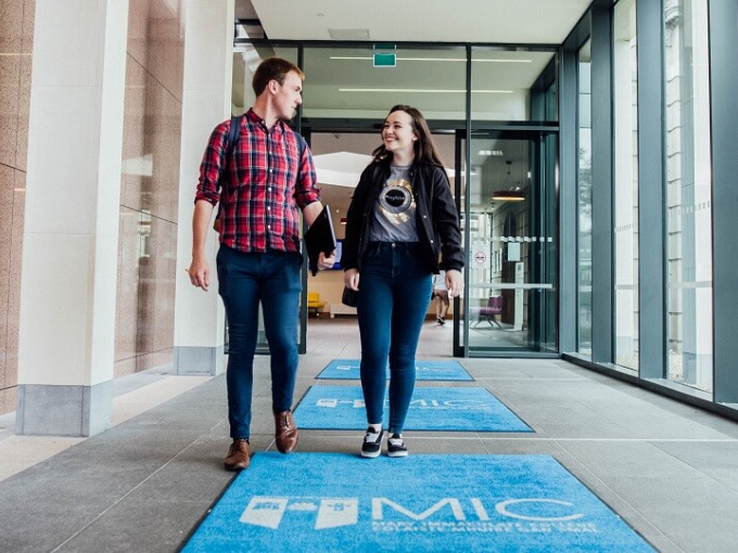 Male & female student walking through main door of MIC Limerick over branded mat to promote Open Day 2019